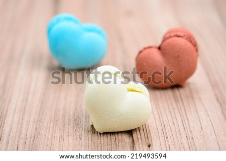 A lot of french colorful macarons in  heart shape on a woody floor - stock photo