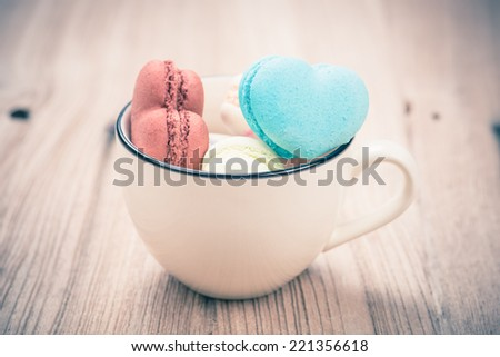 A lot of french colorful macarons in  heart shape on a woody floor in vintage tone style,macarons in a cup - stock photo