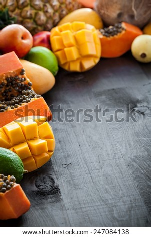 A lot of fresh exotic tropical fruits on wooden background with free copyspace - stock photo