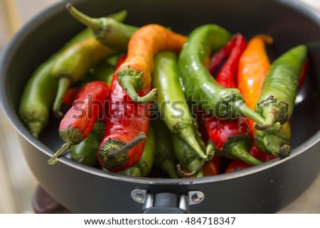a lot of hot chili peppers of different colors in the pan