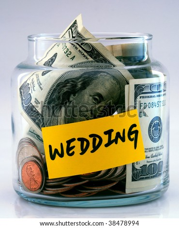 A lot of money in a glass bottle labeled â??Weddingâ? - stock photo