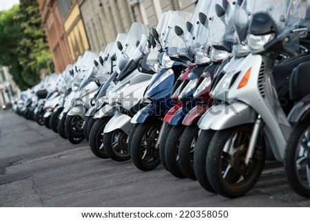a lot of motor scooters parked in a row - stock photo
