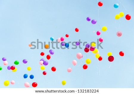 A lot of multi-colored balloons into the sky. - stock photo
