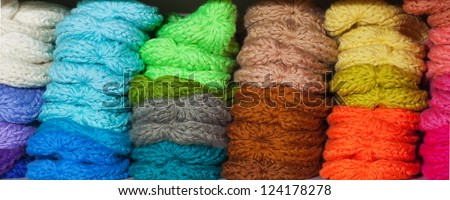 A lot of multicolored hats on the shelf - stock photo