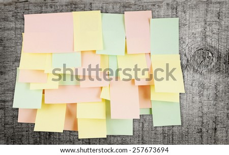 A lot of note papers on grunge wooden background - stock photo