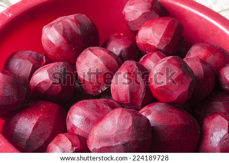 A lot of purple beetroots, in a red, plastic bowl