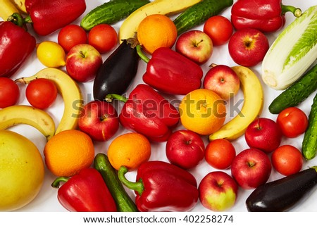 A lot of ripe fruit and vegetables are spread out on a white background - stock photo