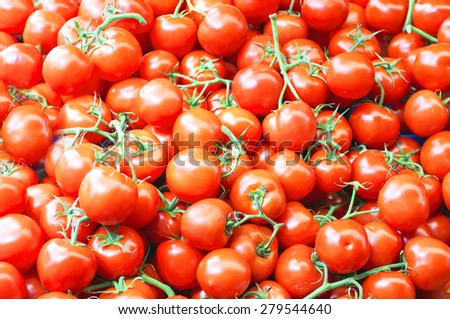 A lot of ripe red cherry tomatoes on the market close up