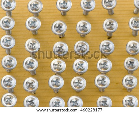 A lot of screws on wood background