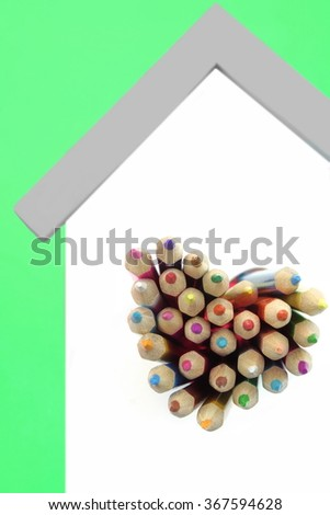 A Lot Of Sharped Colored Pencils Are Sticking Out From The Heart Shaped Window In The Home White Wall Isolated On Green Background, Vertical Image - stock photo