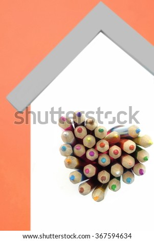 A Lot Of Sharped Colored Pencils Are Sticking Out From The Heart Shaped Window In The Home White Wall Isolated On Orange Background, Vertical Image - stock photo