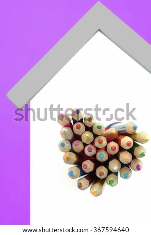 A Lot Of Sharped Colored Pencils Are Sticking Out From The Heart Shaped Window In The Home White Wall Isolated On Purple Background, Vertical Image - stock photo
