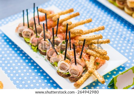 A lot of tasty fresh appetizers + bacon fish bread salad canape, crispy cheese sticks with smoked salmon and dill - stock photo