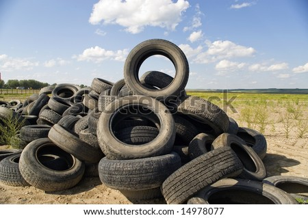 A lot of Wheel Tires dumped in a landfill. - stock photo