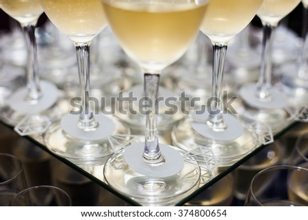 A lot of wine glasses with white tasty wine or champagne on the table at the ceremony. Close up Glasses with alcoholic drinks. - stock photo