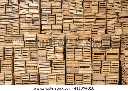 A lot of wooden crates stacked in the high wall.Background lot of wooden boxes - stock photo