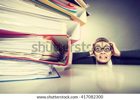 A lot of work and overwork concept. Terrified young businesswoman secretary with huge stack of binders. Scared accountant surrounded of to much work to do. - stock photo