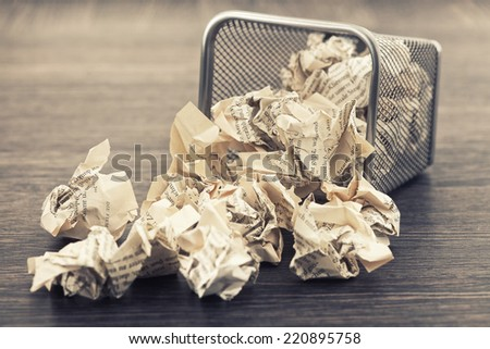 A lot of wrinkled paper laying in and around a wastepaper basket.picture is toned. - stock photo