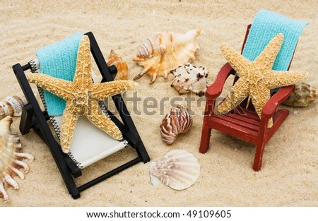 A lounge chair with starfish on a sand background, Relaxing on Vacation - stock photo