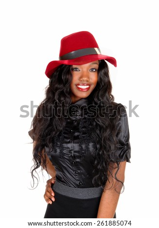 A lovely African American woman in a black blouse and long black curlyhair with a red hat, isolated for white background. - stock photo