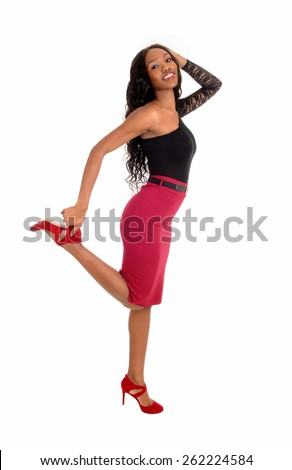 A lovely African American woman in a red skirt and black blouse holdingher leg up, smiling, isolated for white background. - stock photo