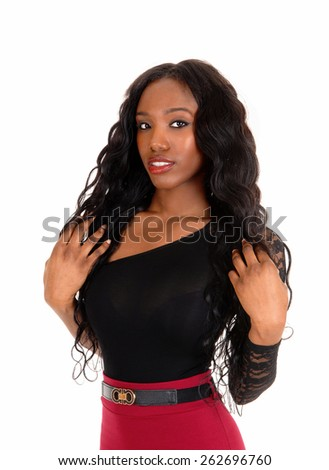 A lovely African American woman in a red skirt and black blouse standing