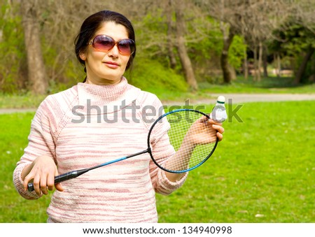 A lovely asian woman playing badminton. - stock photo