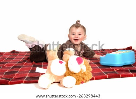 A lovely baby girl in a brown dress lying on a blanket on the floor, isolated for white background.