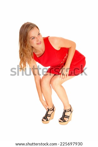 A lovely beautiful young woman standing in a red dress, bending down fixing her heels, isolated for white background.  - stock photo