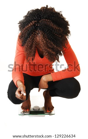 A lovely black teen girl crouching on a scale, looking on her little weight, for white background in an orange sweater and black tights. - stock photo