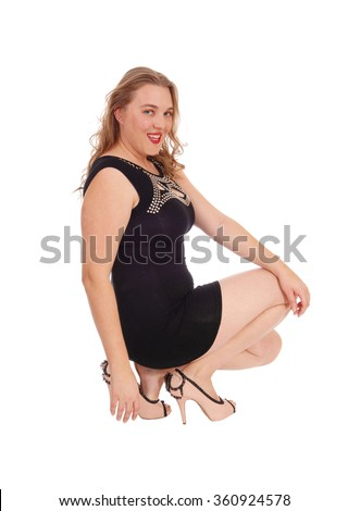 A lovely blond woman in a black dress and high heels crouching on the floor smiling into the camera, isolated for white background. - stock photo