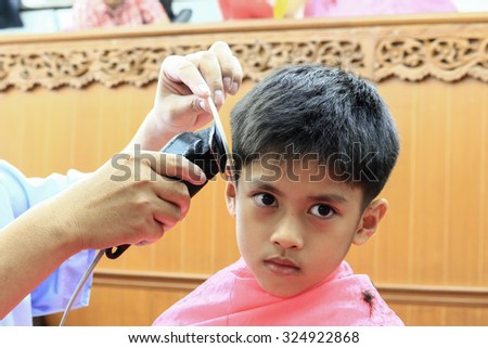 A lovely boy Asian people are  smilier  happily, while cutting the hair in the barber shop