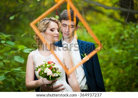 a lovely couple is taking funny photograph for their wedding, taking a frame in front of their faces