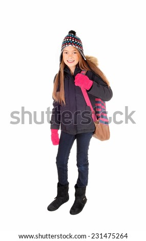 A lovely eight year old girl with long blond hair, a hat and mittens with her backpack over her shoulder, isolated on white background.  - stock photo