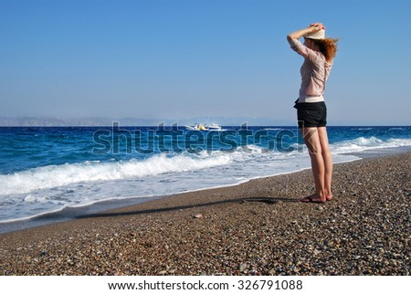 A Lovely Girl with Curly Hair in a Hat Watching the Aegean Sea at the Sunny Beach - stock photo