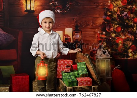 A lovely, little boy in Santa Claus hat holding red oil lamp and opens a big box with gifts on Christmas background.