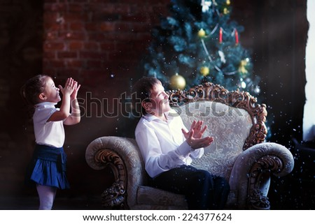 A lovely little girl and a young handsome boy looking through the window in front of the decorated Christmas tree and waiting for a miracle - stock photo