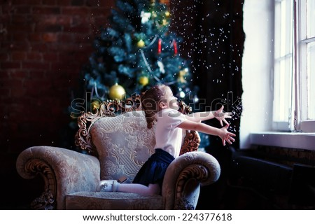 A lovely little girl sitting on the sofa and looking through the window in front of the decorated Christmas tree and waiting for a miracle spreading her hands to the window. - stock photo