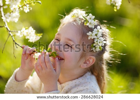 A lovely little girl with a diadem of white flowers standing under a blooming cherry tree on a sunny spring day. Kids and flowers close up.