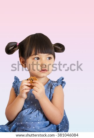 A lovely little girl with piggy tails eating cookie isolated on sweet pink background - stock photo
