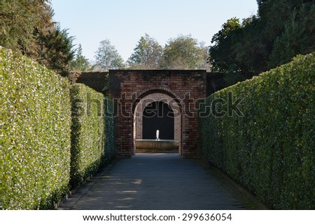 A lovely row of hedges ending with a vintage brick archway and a fountain with the sunlight gracing the water. Wonderful for anything related to gardening, horticulture, advertisements, or other ideas - stock photo