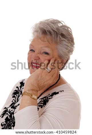 A lovely senior woman in her seventies holding her hand on her face andsmiling, isolated for white background. - stock photo