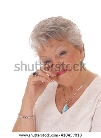 A lovely senior woman in her seventies holding her hand to her face andlooking surprised, isolated for white background. - stock photo