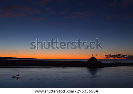 A lovely silhouette of the horizon at the entry of the Whakatane River in Whakatane, New Zealand. This was taken about 30 minutes after sunset on a chilly, winter evening in July. Good for many ideas. - stock photo