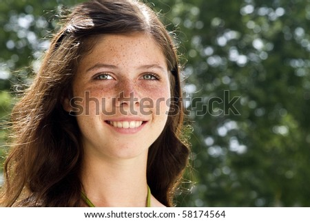 A lovely smiling freckled faced teenage girl with sunlit hair gazes off into the distance. - stock photo