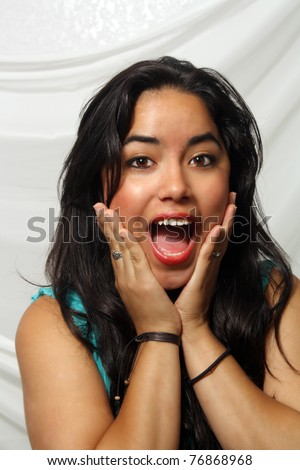A lovely teenage Latina with a friendly, excited, and surprised facial expression.