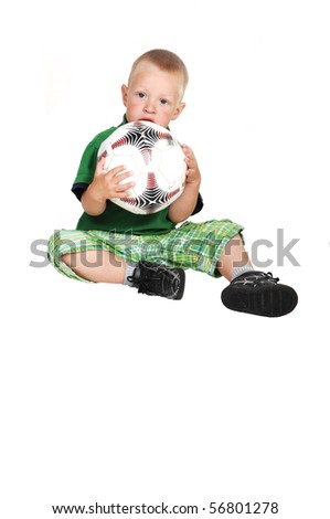 A lovely toddler sitting on the floor in the studio holding up a big soccer ball, on white background. - stock photo