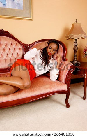 A lovely young African American woman in a red skirt lying on a couch and