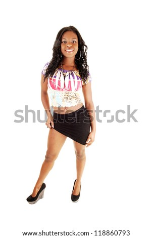 A lovely young black woman standing for white background in the studio smiling and lifting her short black skirt.