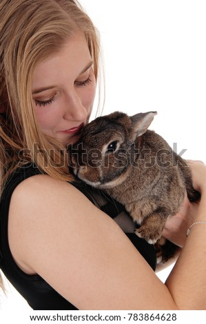 A lovely young blond woman standing in profile closeup and holding a